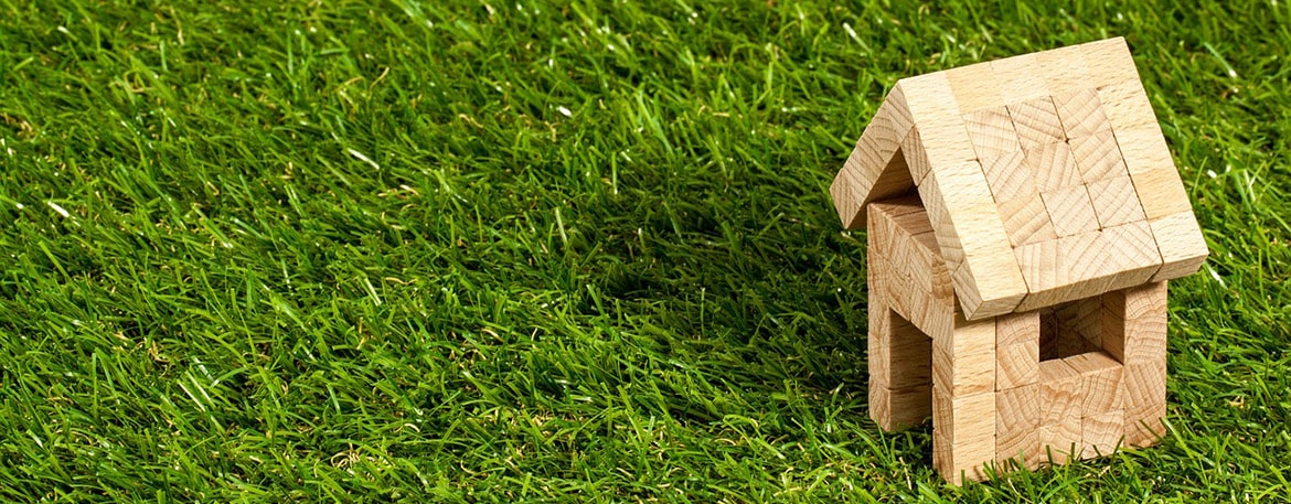 Wooden model home sitting in grass